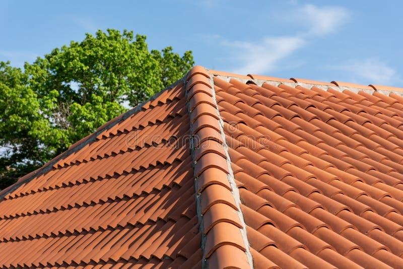 Orange modell för taktegelplatta över blå och molnig vårhimmeldag och grönt träd i bakgrunden arkivfoton