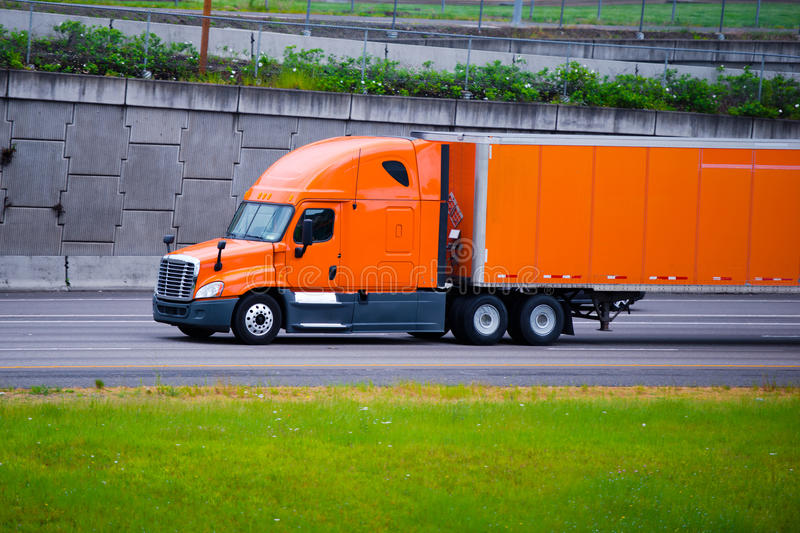 Orange modern semi truck and orange trailer on city road. Modern long haul commercial cargo pro power bright orange big rig semi truck with trailer and stock image