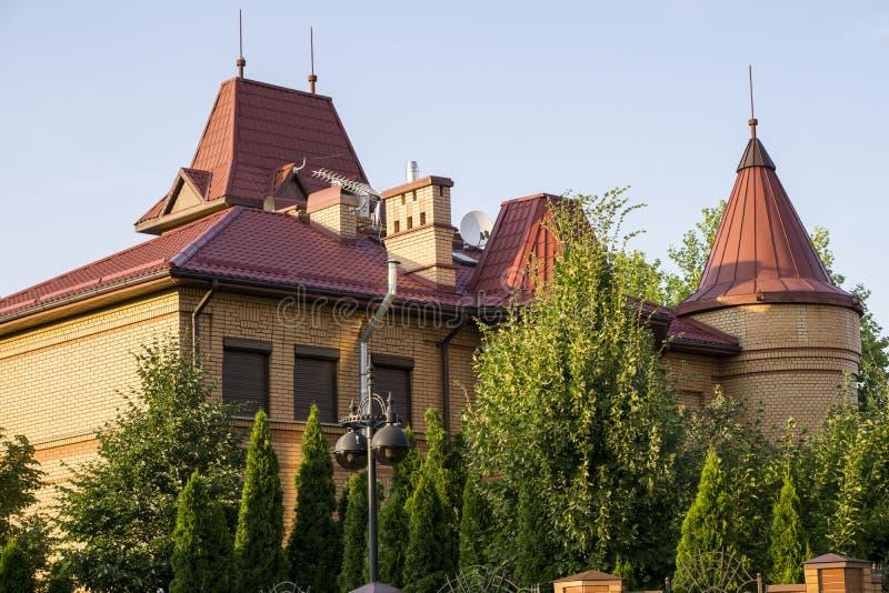Orange modernes Landhaus mit rotem Dach, Garten von Bäumen stockfoto