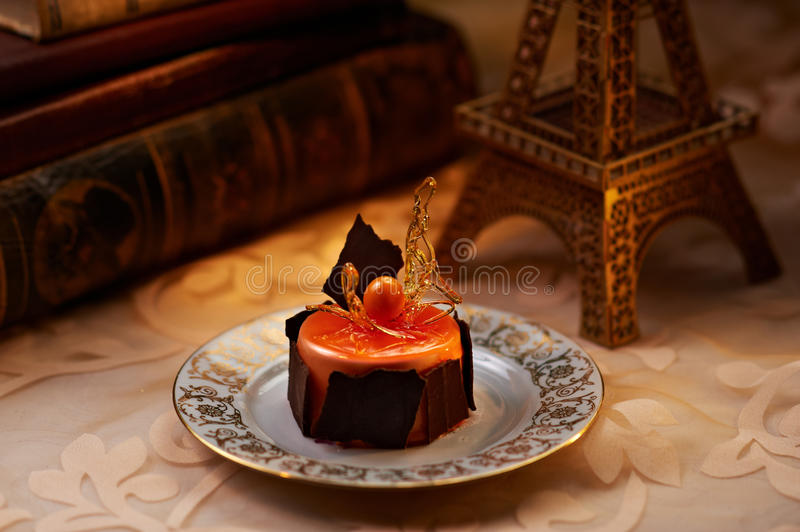 Orange mousse cake. Fresh orange mousse dessert on the plate in interior. Old books and Eiffel Tower miniature can be seen on background royalty free stock image