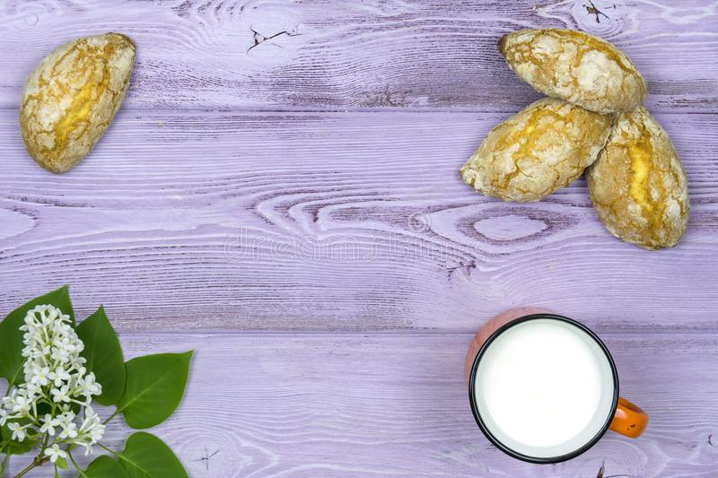 Flat lay. Orange mug with milk. Homemade sweet cookies. Sprig and white lilac flowers on the table. stock photo
