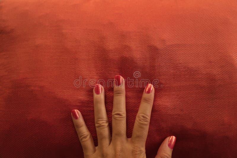 Orange Nagellack-Hand mit Schalen-Haut auf zusammenpassendem Kissen lizenzfreie stockfotos