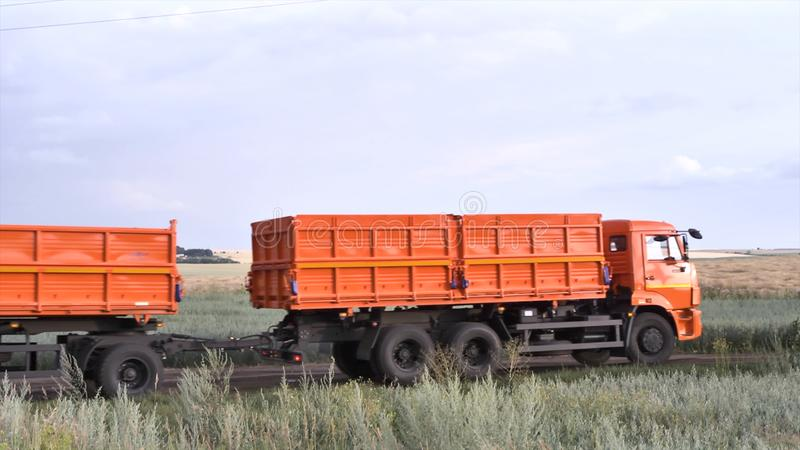 Orange, new ruck with trailer moving on country road on green and yellow field background. Scene. Lorry with a trailer stock photos