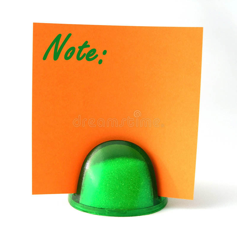 Orange Note Note. Orange note paper with the word Note in a green plastic paperweight holder. Semi isolated with shadow royalty free stock photos
