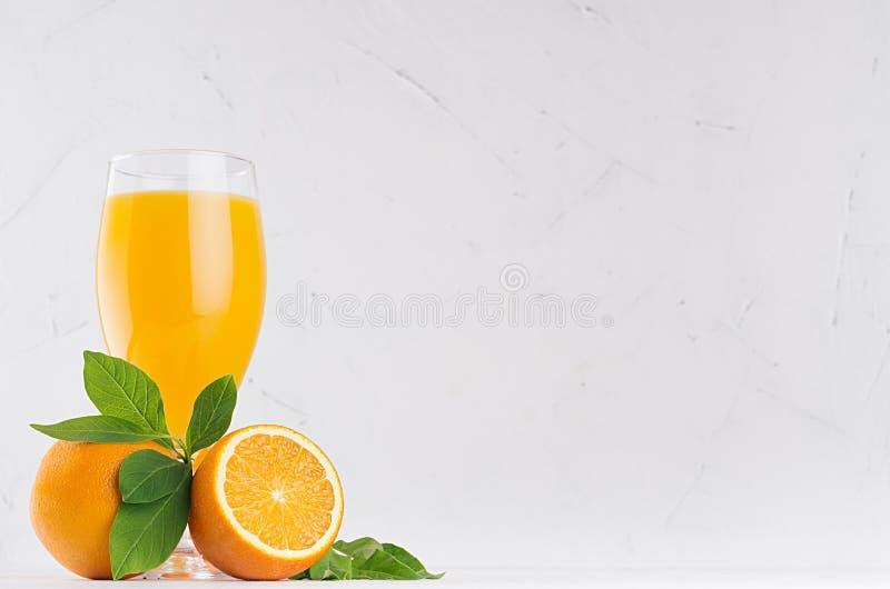 Orange ny citrus fruktsaft med mogna apelsiner och det gröna bladet på det mjuka vita wood brädet, kopieringsutrymme royaltyfri foto