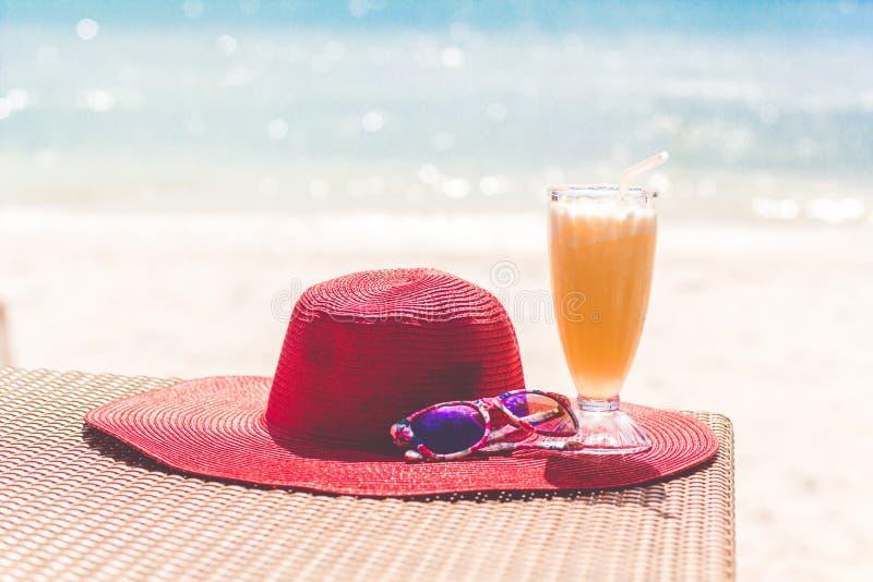 Orange ny fruktsaft, hatt och solglasögon över havet arkivbilder