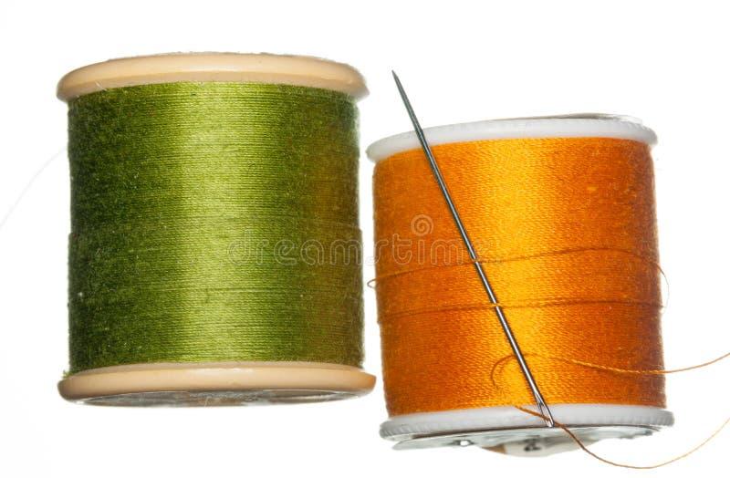 Orange och gröna spolar av tråden arkivbild