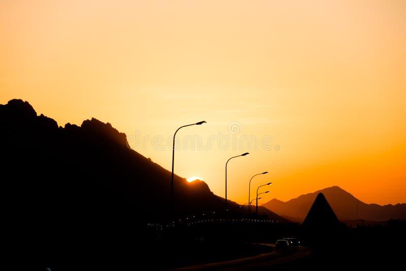 Orange och gul aftonhimmel, soluppsättning bak berg, färgrik solnedgång i Muscat, Oman arkivfoto