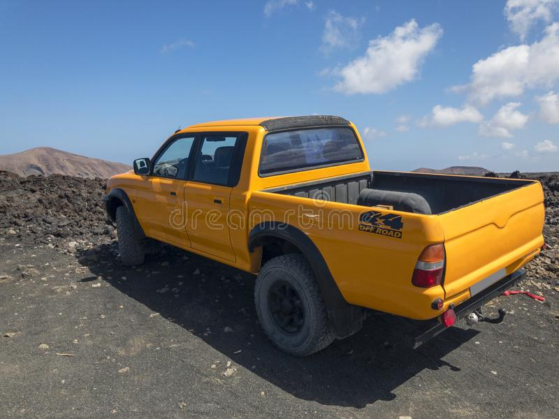 Orange off road vehicle, parked in lava fields, Lanzarote, Spain. Volcanic background on the horizon. Canary Islands royalty free stock images