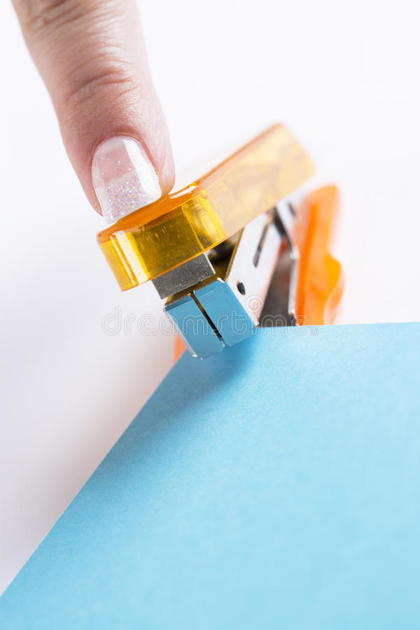Orange office stapeler and blue cardboard. On white table stock photography