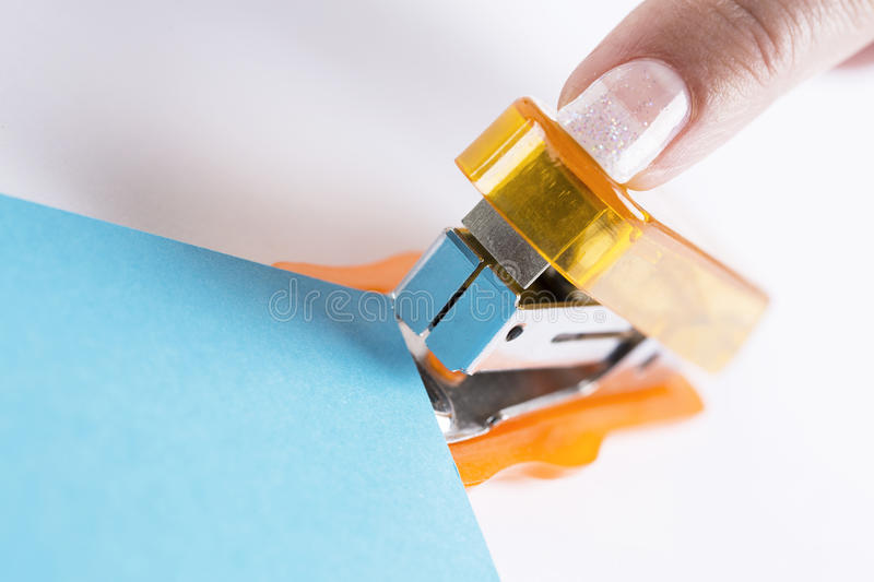 Orange office stapeler. And blue cardboard on white table stock photo