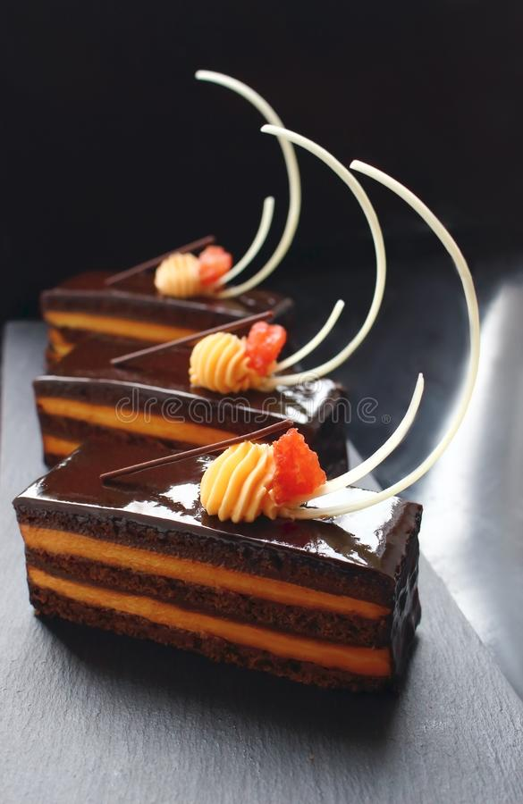 Orange Opera cake slices with citrus ganache and white chocolate decorations royalty free stock image