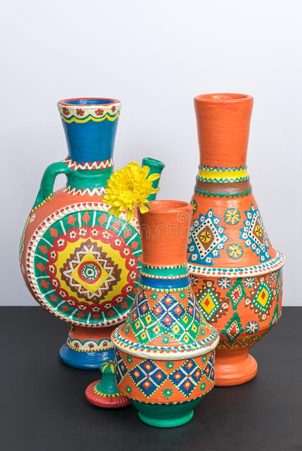 Orange ornate pottery vases on black table and white wall royalty free stock photo