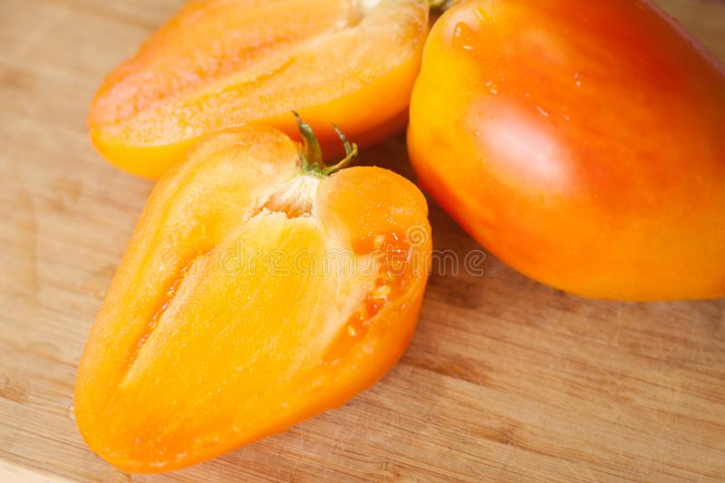 Orange oxheart heirloom tomatoes. Horizontal natural light photo of orange heart shape heirloom cuted tomatoes stock images