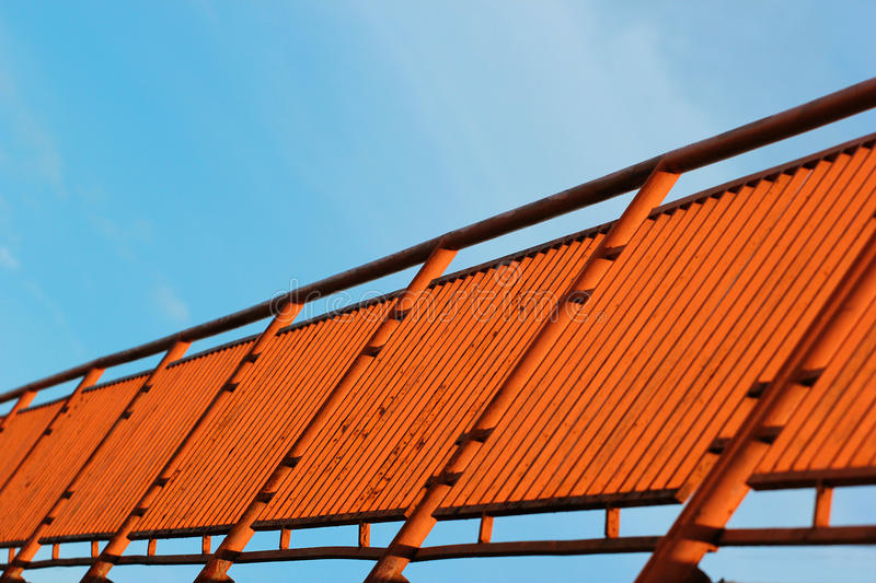 Orange painted metal fence against blue sky background, perspective view. Focus is in the middle stock photos