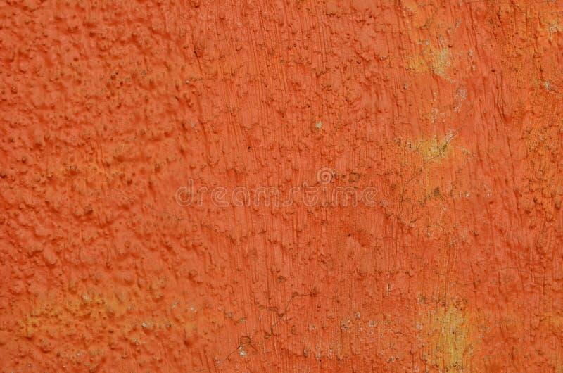 Orange painted plaster. Plaster coating airbrushed with vivid orange graffiti paint stock images