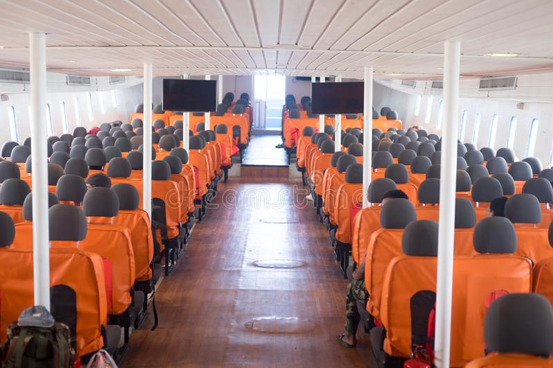 An orange passenger seat in a passenger boat. With life vest, Inside of boat royalty free stock photo