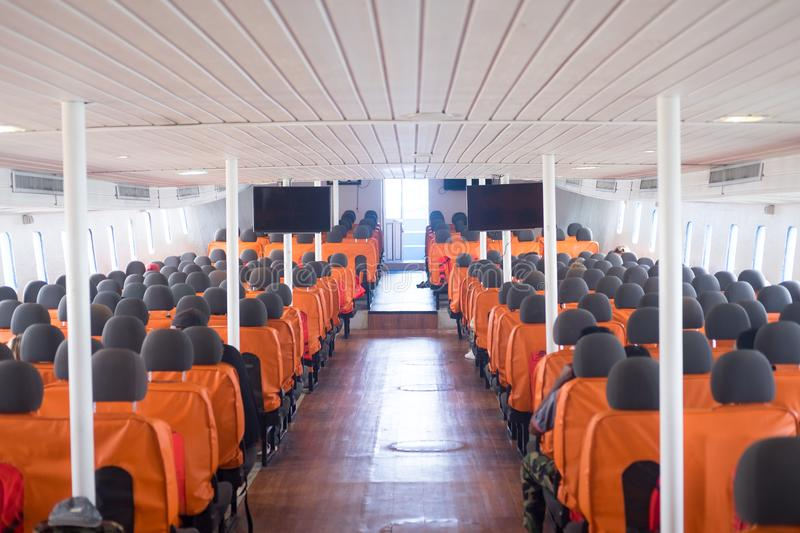 An orange passenger seat in a passenger boat. With life vest, Inside of boat royalty free stock photography