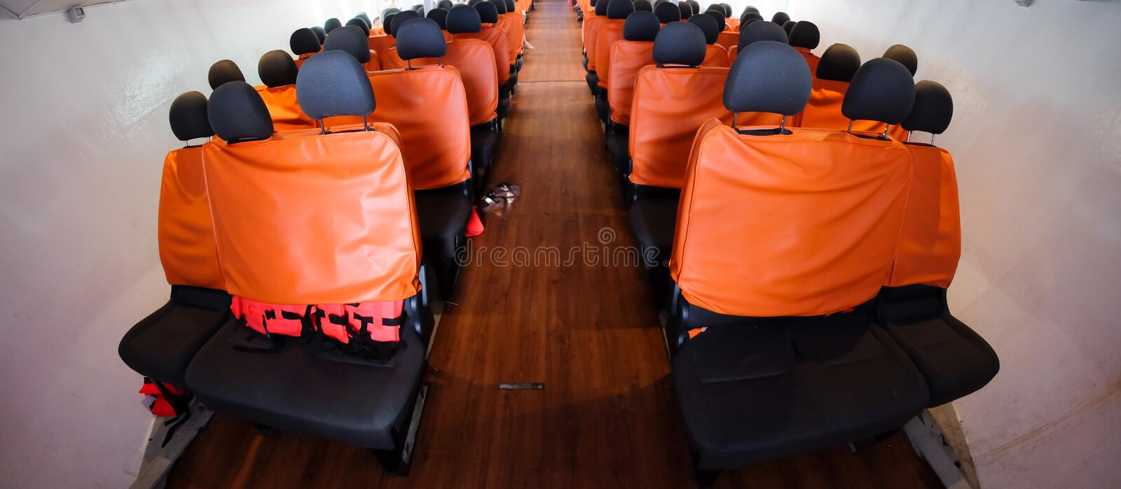 An orange passenger seat in a passenger boat. With life vest stock image