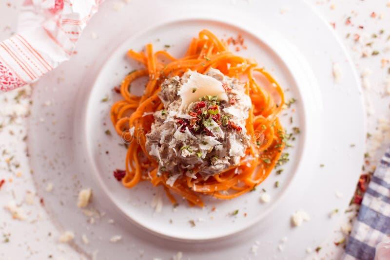 Orange pasta och vit sås tjänade som på den vita plattan arkivbilder