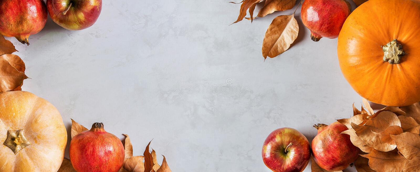 Orange and peachy pumpkins ripe organic red glossy apples pomegranates chestnuts dry golden autumn leaves on gray marble stock images