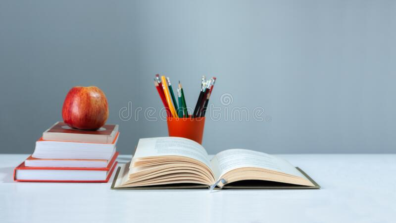 Orange pencil holder, open hardback book, diary, fanned pages on stack of books on white table with red apple. Books stacking. Back to school concept. Copy stock image