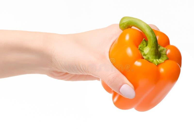 Orange pepper in a hand stock photos