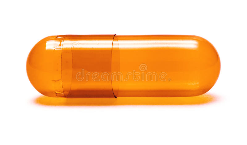 Orange Pill. Macro of a single orange, transparent pill isolated on white royalty free stock photos