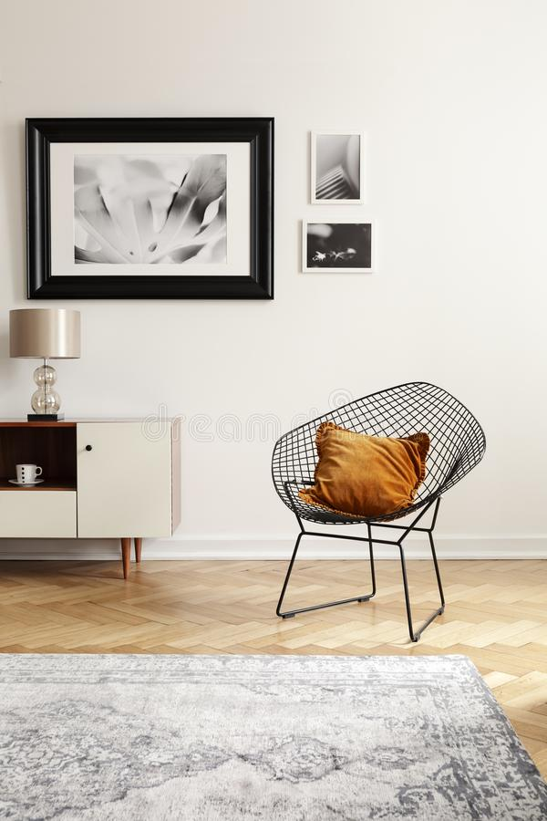 Orange pillow on a black, industrial net chair by a white wall with gallery of mock-up pictures in an elegant living room interior vector illustration