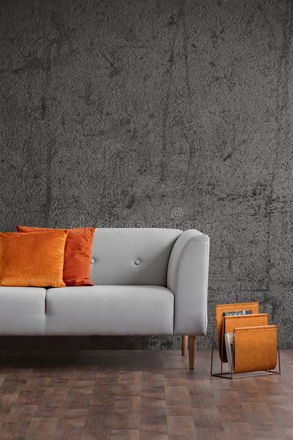 Orange pillows on grey couch in dark loft interior with concrete wall and wooden floor. Real photo stock images