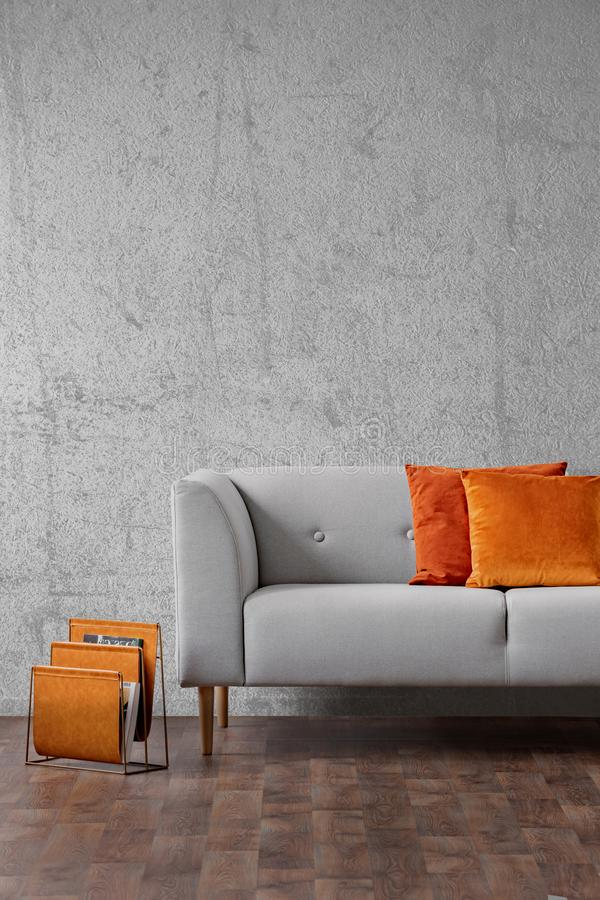 Orange pillows on grey settee in living room interior with concrete wall and wooden floor. Real photo.  royalty free stock photo