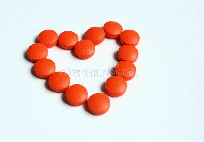 Orange pills that are composed to shape of heart isolated on white background. Love to medicine stock photography