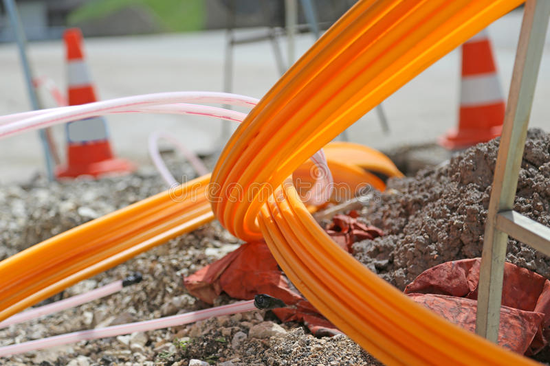 Orange pipes for fiber optics in a large city road construction royalty free stock photography