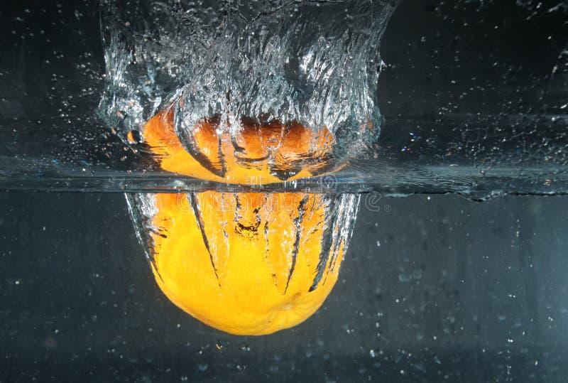 Orange plaska in i vattnet arkivbild