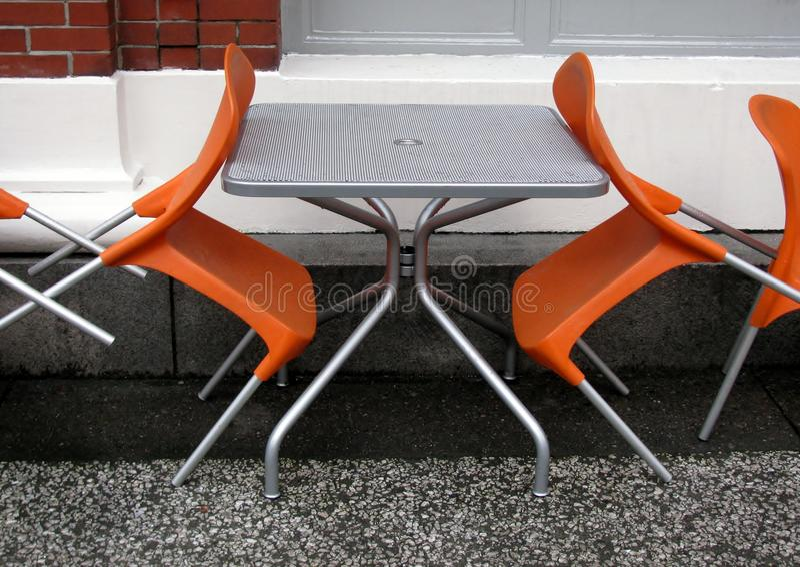 Orange plast-stolar och metalltabell i ett gatakafé efter regn royaltyfria bilder