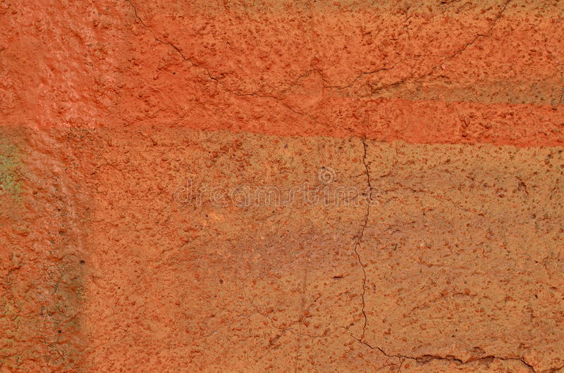 Orange plastered wall. Cracked plastered wall airbrushed with orange graffiti paint stock images