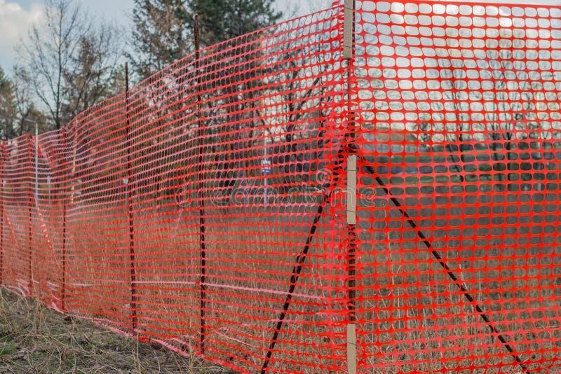Orange plastic construction mesh safety fence stock image