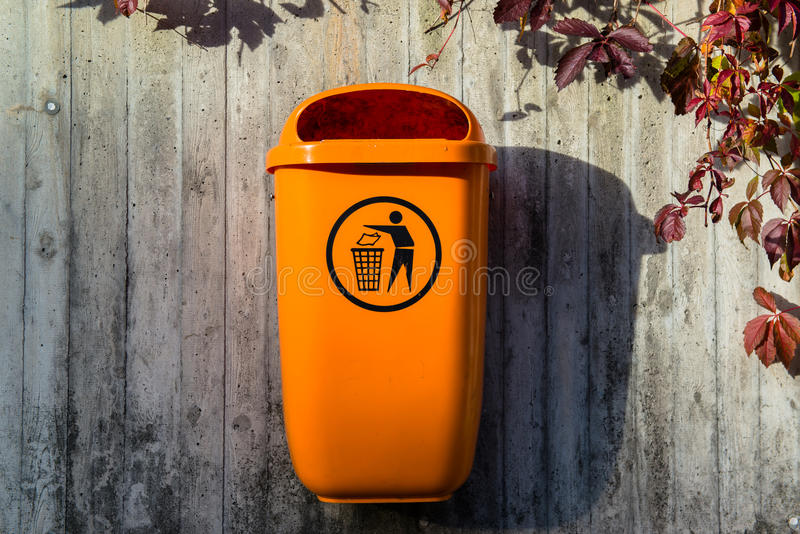 Orange plastic dust bin. In an old medieval european town stock image