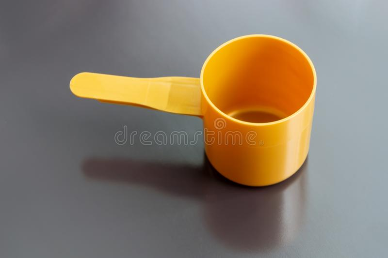 Orange plastic measuring dosage spoon on dark background royalty free stock photos