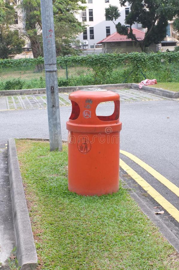 Orange plastic trash can on in public place stock photos