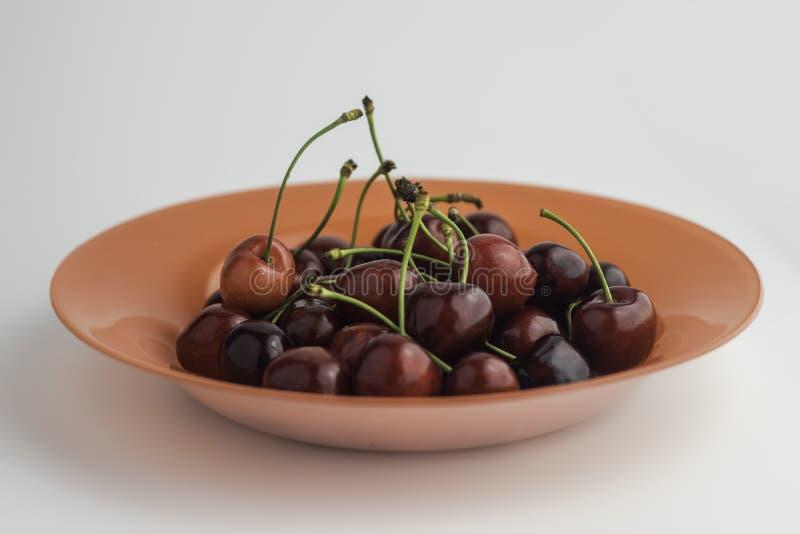 Orange plate full of sweet red cherries stock photo