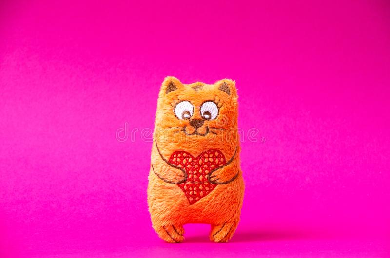 Orange plush cat with red heart so cute on the pink background royalty free stock images
