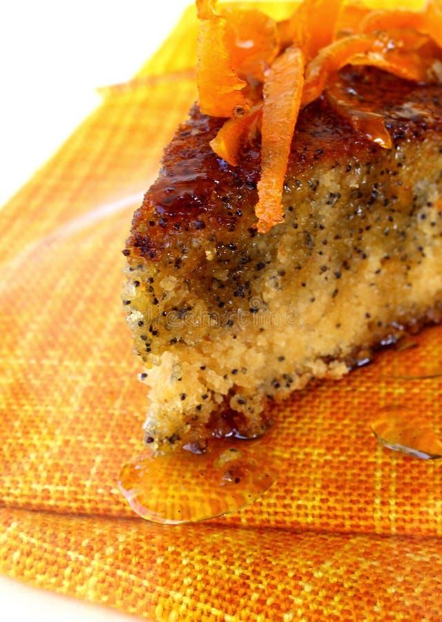Orange poppy seeds tart. An orange poppy seeds sweet tart slice with orange syrup royalty free stock image