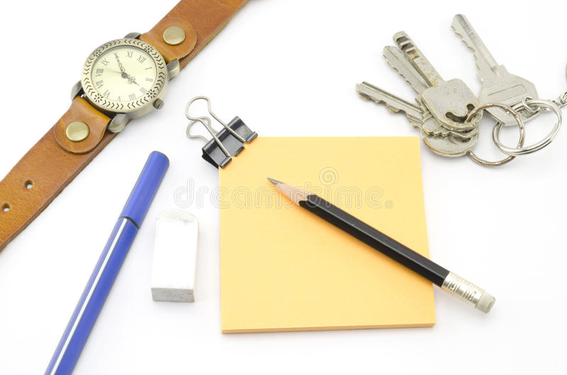 Orange Post It With Keys Watch And Bulldog Clip And Black Pencil Stock Photos