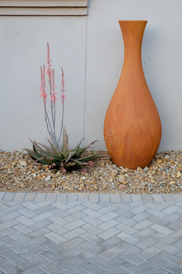 Orange pot with aloe. An orange textured pot with aloe desert plant with pink flowers stock photo