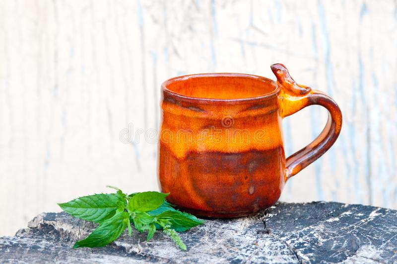 Orange pottery mug. With bird on handle stock photography