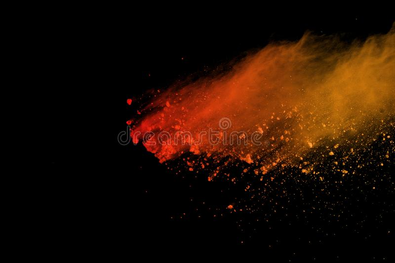 Freeze motion of colored powder explosion isolated on black background. Abstract of Multicolor dust splatted. Orange powder explosion isolated on black royalty free stock images