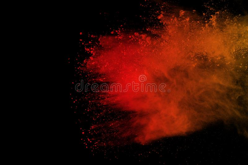 Freeze motion of colored powder explosion isolated on black background. Abstract of Multicolor dust splatted. Orange powder explosion isolated on black stock images