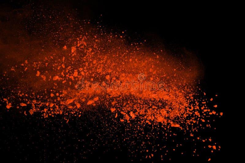 Orange powder explosion isolated on black background. Freeze motion of colored dust splatted. royalty free stock image