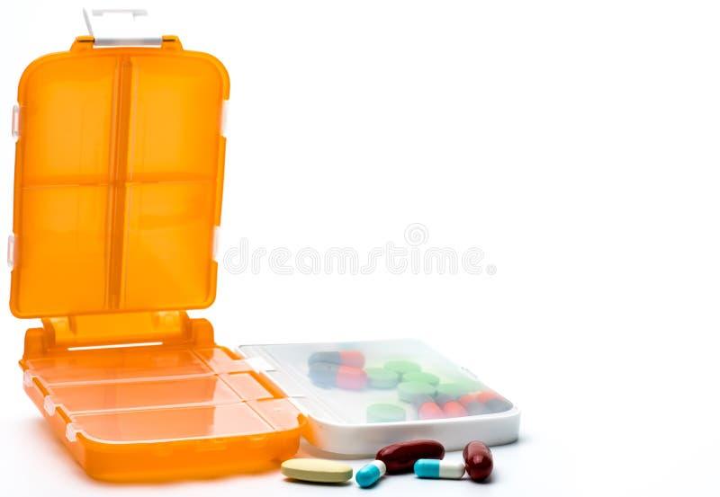 Orange preventivpillerar boxas med minnestavlor och kapselpreventivpillerar som isoleras på vit bakgrund med kopieringsutrymme arkivfoton